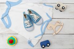 Baby bodysuit with shoes and kids toys. Flat lay Royalty Free Stock Images