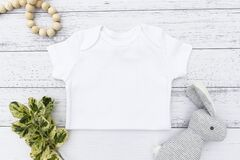 Baby bodysuit vest half on a white wood background