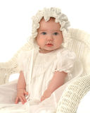 Baby in Bonnet. Baby girl in bonnet, sitting in wicker chair Royalty Free Stock Photos