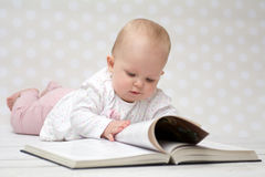 Baby with the book. Baby girl lying on the belly reading a book Royalty Free Stock Photo