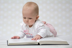 Baby with the book. Baby girl lying on the belly reading a book Stock Image