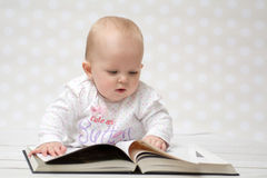 Baby with the book. Baby girl lying on the belly reading a book Royalty Free Stock Images