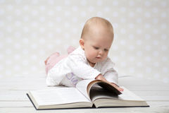 Baby with the book. Baby girl lying on the belly reading a book Stock Photography