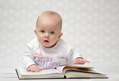Baby with the book. Baby girl lying on the belly reading a book and looking at the camera Stock Image