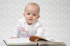 Baby with the book. Baby girl lying on the belly reading a book and looking at the camera Royalty Free Stock Photo