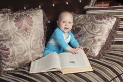 Baby with book. Baby sitting on the couch with book Stock Photography