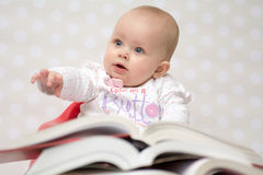Baby with books. Cute baby girl sitting behind a pile of books Stock Photos