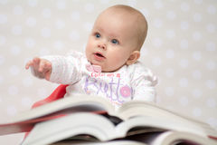 Baby with books. Cute baby girl sitting behind a pile of books Stock Photography