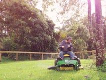 Baby boomer maaiend gras op rit op maaimachine Royalty-vrije Stock Foto