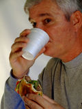 Baby Boomer Man eating hamburger Royalty Free Stock Photography