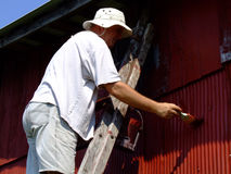 Baby boomer Man painting old garage. Senior man on ladder painting an old building Stock Images