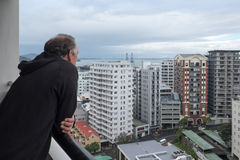 Baby boomer retired man looks at view of apartment buildings in. Baby boomer retired man looks at view of apartment buildings from balcony in Auckland, New Stock Photos
