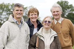 Baby Boomers and Aging Parents. A Baby Boomer son and his wife pose for a family portrait with aging parents outdoors in Autumn royalty free stock photo