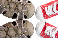 Baby bootees opposite adult sneakers Stock Photography
