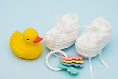 Baby Booties. With baby rattle and rubber duck sitting on a blue background stock image