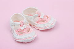 Baby booties. Baby's first booties against a pink background royalty free stock photo