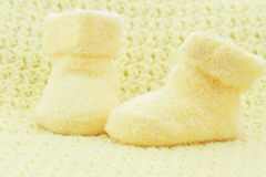 Baby Booties. Yellow baby booties and blanket with room for text royalty free stock photos