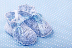 Baby booties. Handmade baby booties on blue background stock photography