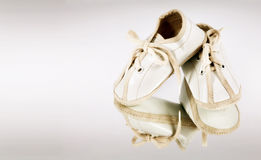 Baby Booties. Tiny white baby booties reflected on background stock photo