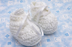Baby Booties. White baby booties on alphabet background royalty free stock image