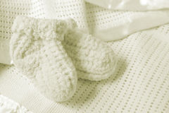 Baby Booties. On a soft baby blanket. Soft and warm for the new arrival stock photos