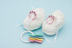 Baby Booties. With baby bracelet and rattle sitting on a blue background Stock Photography