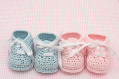 Baby Booties. Blue and pink baby booties on a pink background, baby booties stock image