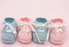Baby Booties. Blue and pink booties on a pink background stock image
