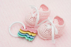 Baby Booties. With key rattle on a pink background stock image