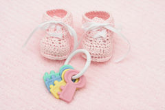 Baby Booties. With key rattle on a pink background stock photography