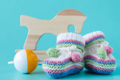 Baby booties with baby rattle sitting on a aquamarine background Stock Images