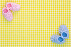 Baby booties background. Kinitted Baby booties for a girl and a boy on a yellow gingham background Stock Image