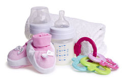 Baby booties, bottles and toy for teething. Composition of infant baby booties, bottles and toy for teething Stock Photo