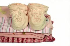 Baby booties and clothes. Baby sleeper booties on baby clothes royalty free stock images