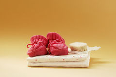 Baby booties, combs and diapers. On a beige background Stock Photos