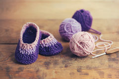 Baby Booties. Crochet baby booties on wooden table stock images