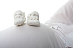 Baby booties on expectant mothers bump. Showing i love mummy and daddy Royalty Free Stock Photos