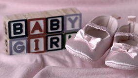 Baby booties falling on pink blanket with baby girl message in blocks
