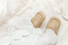 Baby booties on the feet. Of the baby Royalty Free Stock Photos