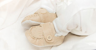 Baby booties on the feet. Of the baby Royalty Free Stock Image
