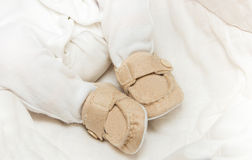 Baby booties on the feet. Of the baby Royalty Free Stock Photo