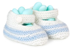 Baby booties full of dragee. Crochet baby booties filled with blue sugared almonds stock photos
