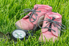 Baby booties. Good direction - little baby booties in the grass with compass Stock Photos