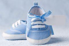 Baby booties. Little baby booties with a tag on a blue background royalty free stock photo