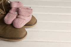 Baby booties and mans shoes on floor Royalty Free Stock Images