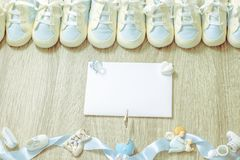 Baby booties for newborn boy shower party, store add or post card. Top view. Copy space. Framing. Baby blue bootees with small cute accessories and white paper Stock Photos