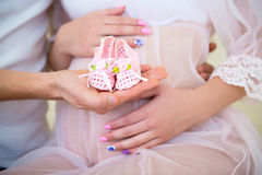 Baby booties for the newborn daughter on a background of a pregnant belly Stock Image