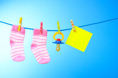 Baby booties, nipple and yellow card on blue Stock Images