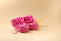 Baby booties and pacifier. On a beige background Royalty Free Stock Photography