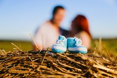 Baby booties and pregnant couple in the field royalty free stock photos
